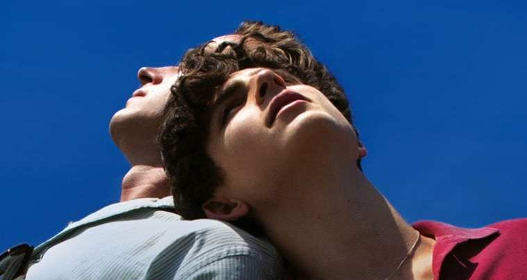 two men lean against each other back to back against a blue sky