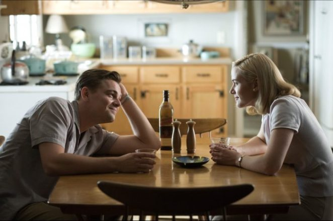 leonardo dicaprio kate winslet man and woman sitting across table from one another talking and drinking and smiling