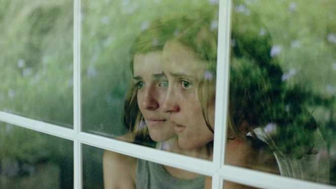 The two daughters look on in Dogtooth.