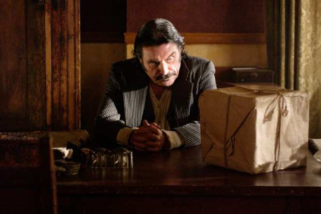 Al looking at the box on his desk in HBO's Deadwood
