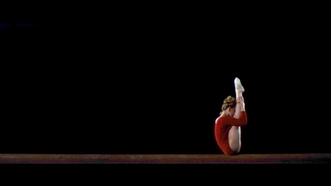 A sitting gymnast pulls her legs to her chest