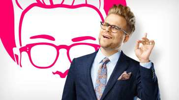 Adam Conover raises a finger in a promo shot for Adam Ruins Everything