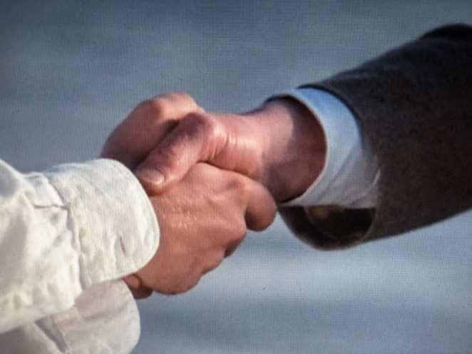 A closeup of Ronnie and Giles shaking hands