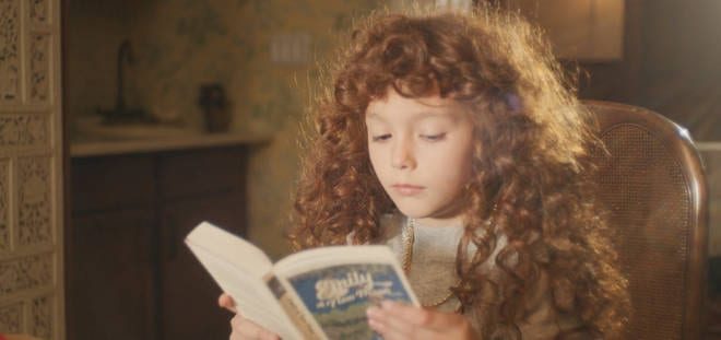 Nadia as a girl, seen in a flashback reading Emily of New Moon.