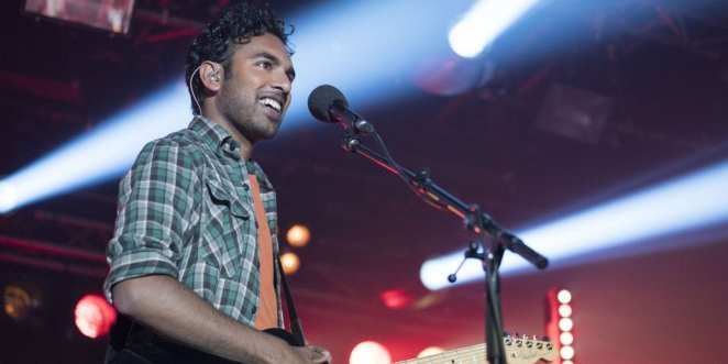Himesh Patel plays an electric guitar on stage