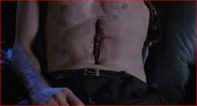 One of the more disturbing body horror images is a vagina like opening in Max's chest where guns and videotapes are to be held and played.