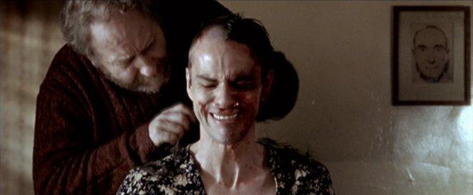 A man cuts a woman's hair in Calvaire as she cries in fear.