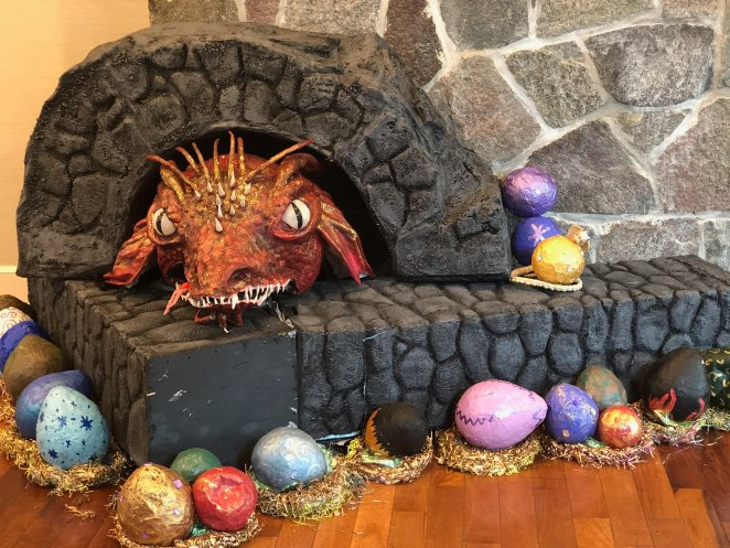 A homemade dragon, surrounded by eggs, decorating the con area