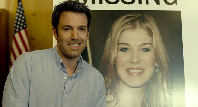 nick smiles in front of missing poster