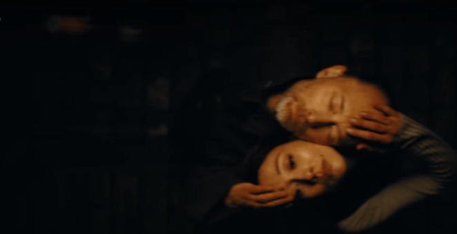 Thom Yorke and a woman rest their heads on each others in the dark