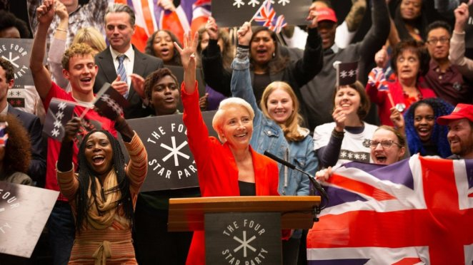 Emma Thompson as Vivienne Rook raises her hand at an event for the Four Star Party