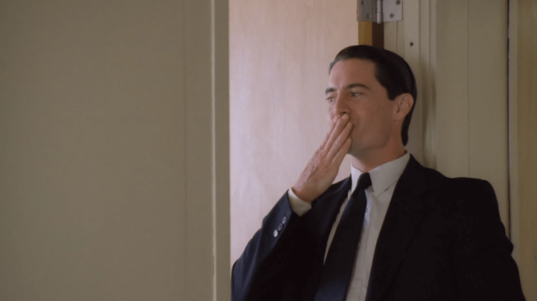 Dale Cooper blows a kiss into the apparent office in which Diane is in