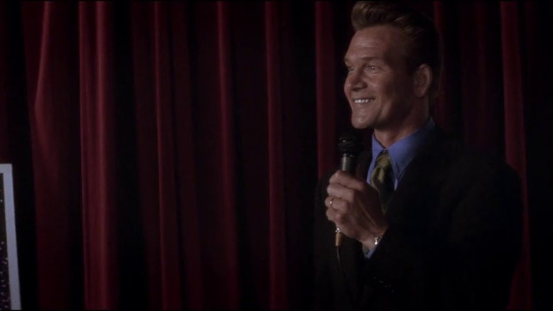 Patrick Swayze as motivational speaker, Jim Cunningham in Donnie Darko, grinning on stage with a microphone