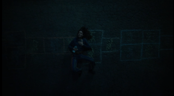 Lenny (Aubrey Plaza) lies on a hopscotch board drawn on the pavement