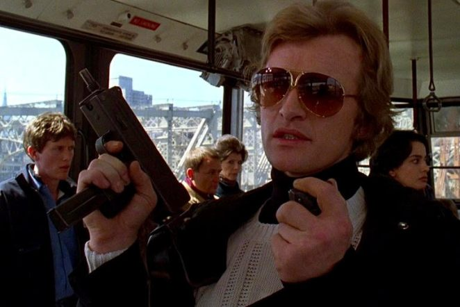 Rutger Hauer wearing a tuxedo and shades and carrying a gun