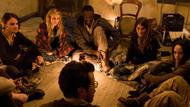 a group of friends sit in a circle on the floor and talk