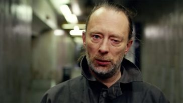 A close-up shot of Thom Yorke's face as he walks down a tunnel