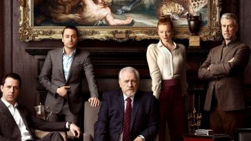 The Roy family pose in front of a mantleplace, above which is a large painting, only a small part of which can be seen