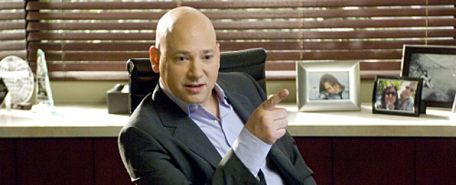 Evan Handler sits in a chair pointing his finger