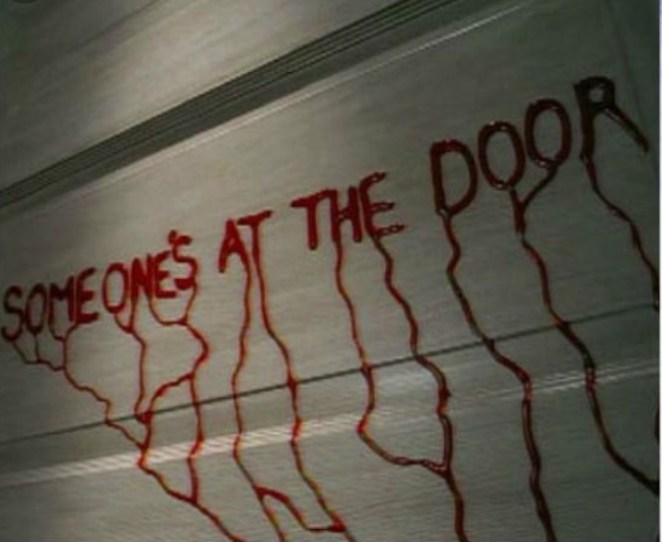 Someone's At the Door written in blood on a wall