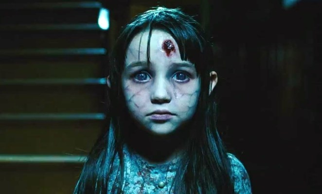 The ghost of a dead girl named Jodie with a bullethole in her forehead stands in the front hallway of a haunted house in The Amityville Horror (2005).