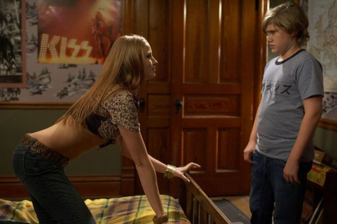 Teenage babysitter Lisa seductively poses on bed while young Billy Lutz observes in The Amityville Horror (2005).