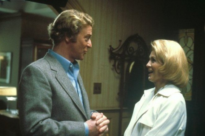 Kate, in a white suite and British man (Michael Caine) in grey suit are in a therapist office