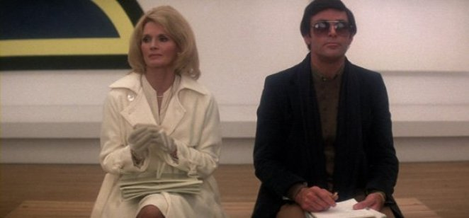 Blonde woman in white suit and man in dark suit and sunglasses sit next to each other in an art museum.