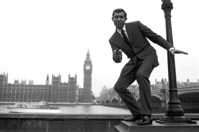 George Lazenby posing on a wall as Bond, with The Houses of Parliament in the background
