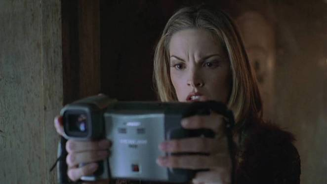 Aspiring TV show host Melissa Marr holds a camera in front of her face, looking scared by what she sees on it.