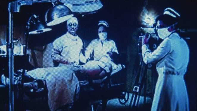 The ghosts of a former Sanitarium perform illegal surgeries on their patients, while looking up at the person filming them.