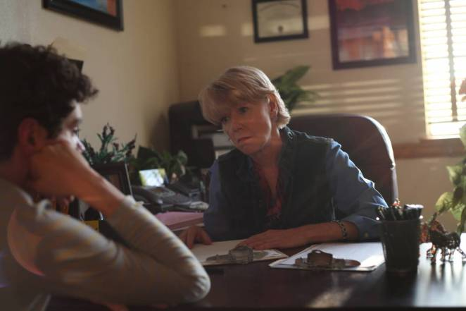 Adrienne King behind a desk in therapy office