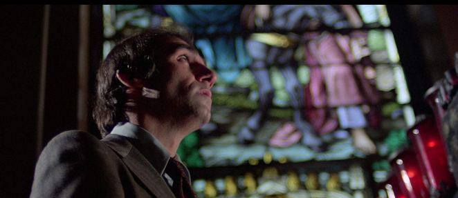 Tony Lo Bianco in God Told Me To (1976) with a stained glass window behind him
