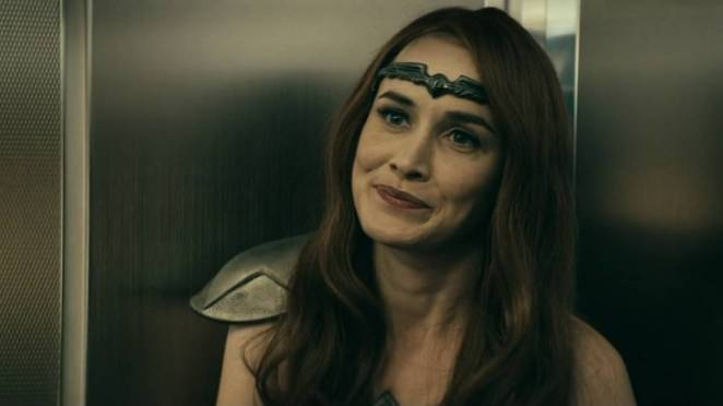 Queen Maeve, in an elevator, with a cynical smirk on her face.