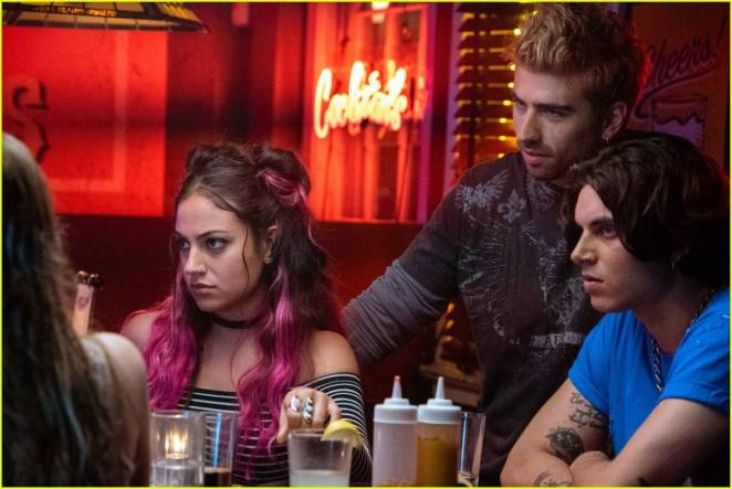 Tessa's roommates, a girl with purple hair and 2 lads sit at a table in a bar