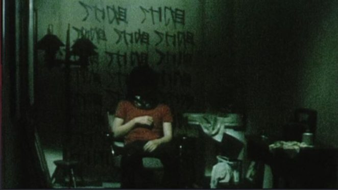 A man in a red shirt sits on a chair in the middle of a room with a black bag on his head in Pulse