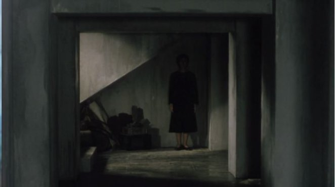 A ghostly woman stands in the right corner of a room in Pulse