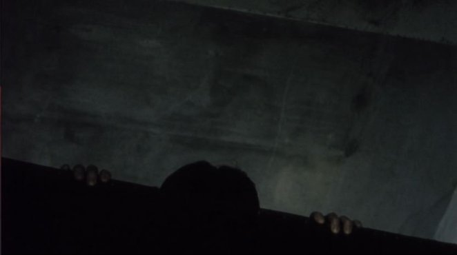 The hands and head of a ghost woman peek over the top of a black couch in Pulse