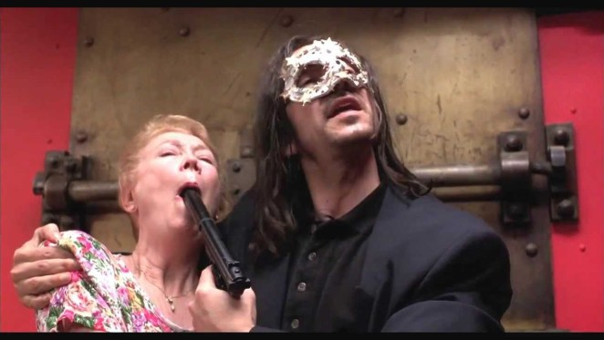 A masked Eric (Jean Hughes-Anglade) holds a gun in an old woman's mouth during a bank robbery