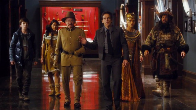 Larry Daley (Ben Stiller) stands in a museum with his right hand raised. His son, Sacajawea, Theodore Roosevelt, Ahkmenrah, and Attila the Hun are behind him.