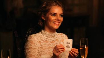Grace holds up the card she has chosen which reads 'Hide and Seek' she is smiling