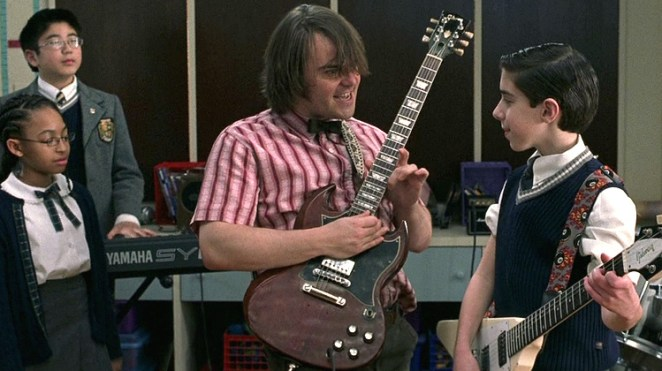 Dewey Finn (Jack Black) plays an electric guitar beside his student Zack. Behind Dewey are his students Lawrence and Alicia.