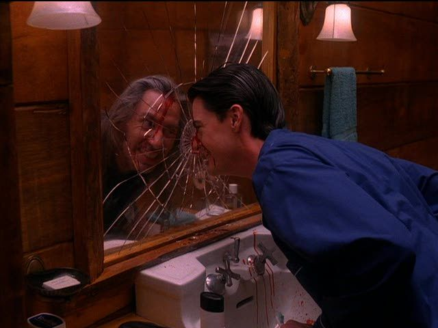 Image of Dale Cooper smashing his face into the mirror and grinning maniacally while staring at BOB in his reflect. Blood streams down his forehead and onto the bathroom sink.