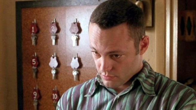 Vince Vaughn as Norman Bates wearing a striped shirt and standing in front of a wall with motel room keys tacked to a board.