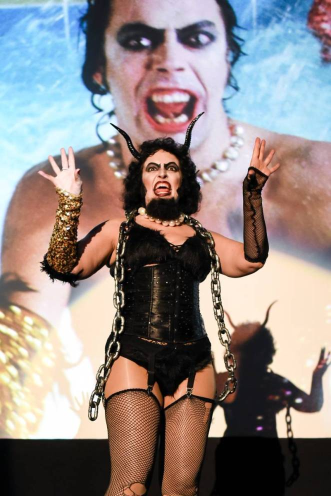 Frank-N-Furter with Krampus horns, beard and chain, singing and dancing in front of movie screen.