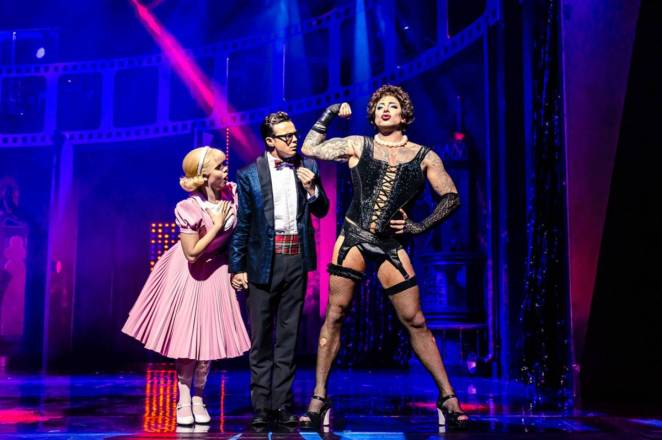 Frank-N-Furter shows off his bicep to Brad and Janet.