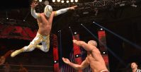 Rey Mysterio Jr leaps off the top turnbuckle onto Cesaro