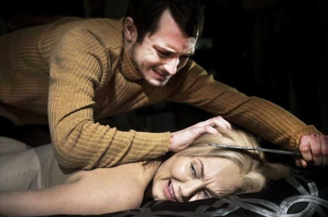 Frank (Elijah Wood) sits on a naked victims back as he cuts her hairline with his knife.