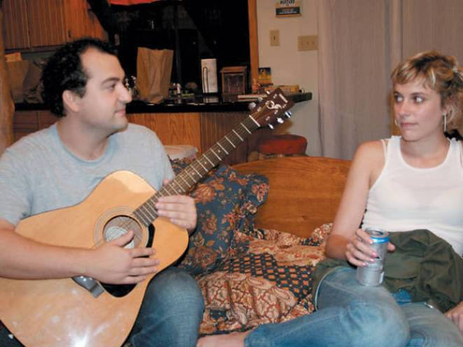Sitting on the sofa, Chad plays the guitar while Michelle listens