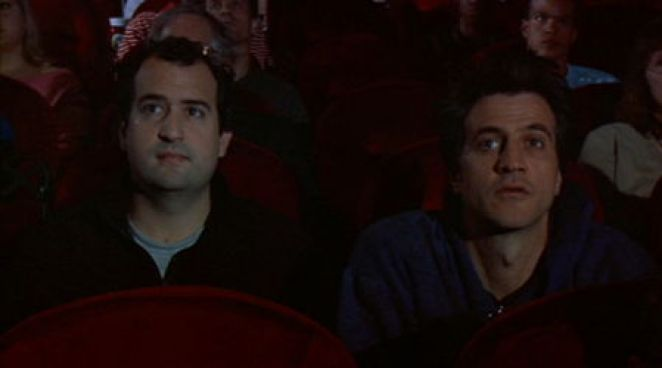 Matt and Chad sitting watching a movie in a theater